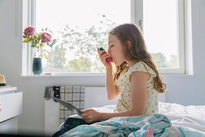 young girl sitting in bedroom using inhaler for asthma