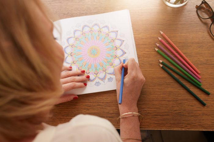 overhead shot of woman drawing in adult coloring book
