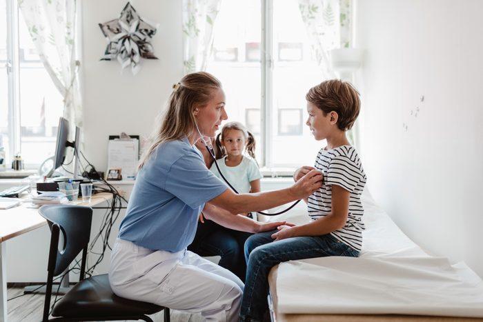 doctor examining young boy