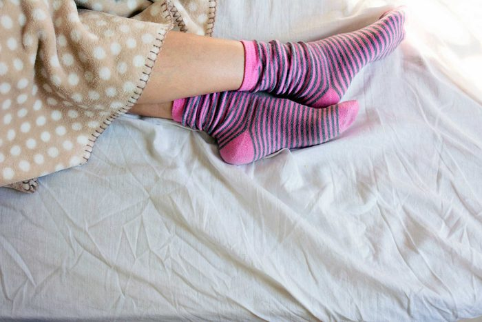 Person wearing cozy pink socks in bed