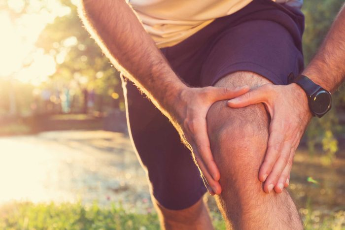 Man in shorts holding his knee as if having knee pain.