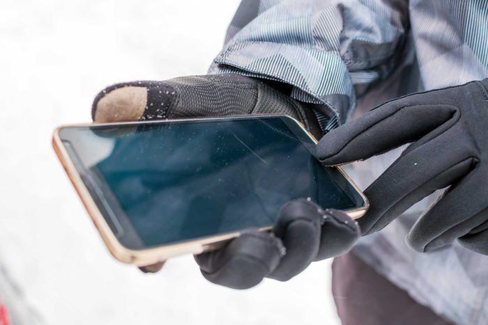 Person uses phone while wearing gloves