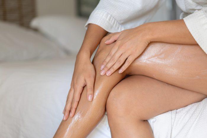 applying body oil moisturizer to legs