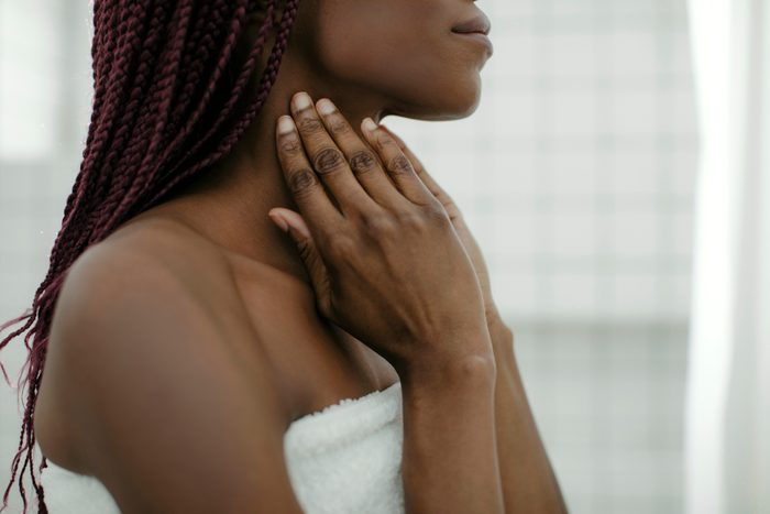 woman applying lotion to neck
