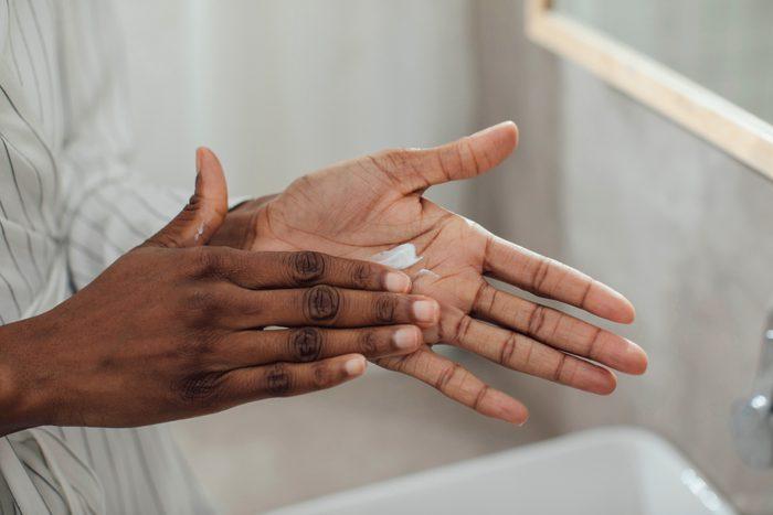 close up of woman moisturizing hands