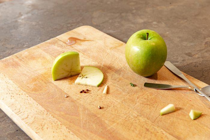 green apple on cutting board in kitchen