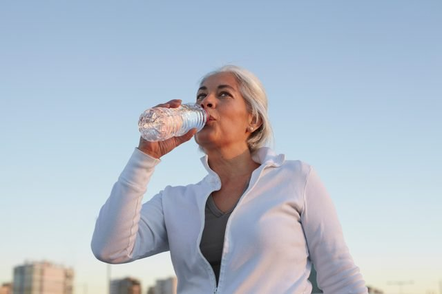 woman drinking water while exercising