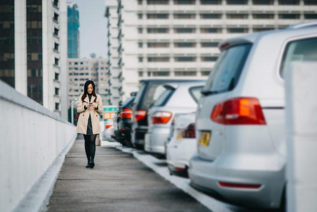 young woman walking through parking lot