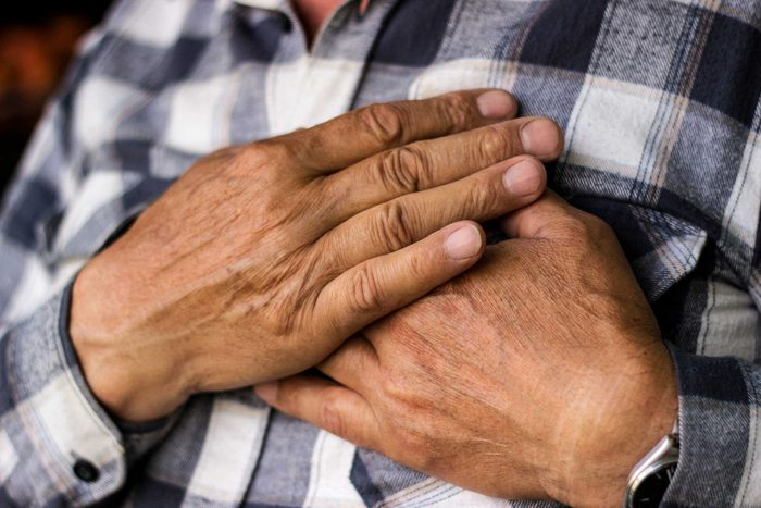 older man holding his hands over his chest