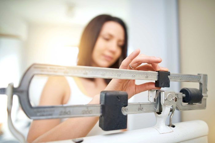 woman weighing herself on a scale