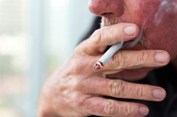 Man with a mustache smoking a cigarette.