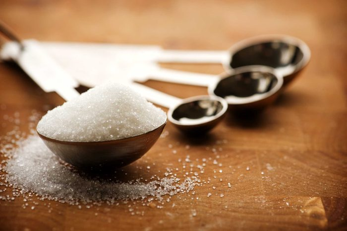 measuring spoons, one full of sugar