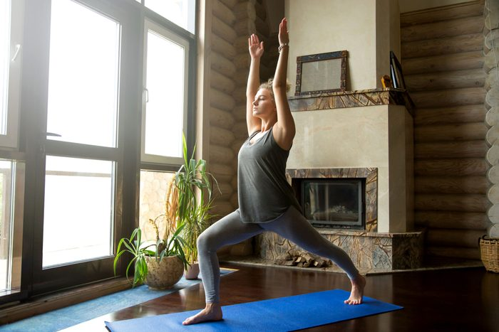 woman doing yoga pose on mat in house