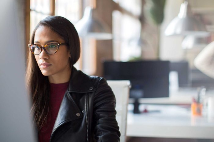 Black woman with glasses working on a computer
