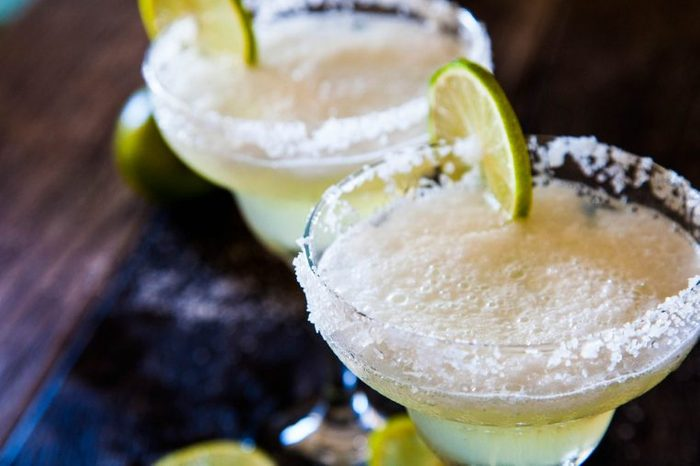 Two glasses of tequila with lime slices.