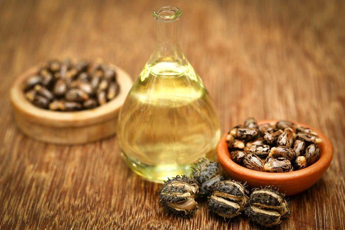 castor oil in a bottle next to bowls of castor beans