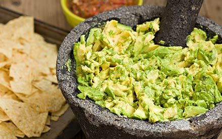 guacamole in a bowl with chips in the background
