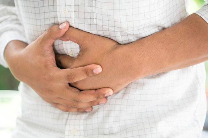 man clenching his stomach in discomfort