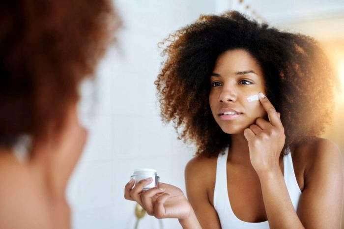 lovely young woman looking in mirror and putting on face cream