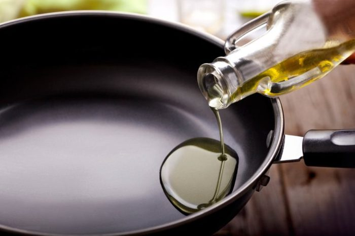 oil being poured into a cooking pan