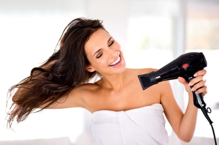 woman using an attachment on her blow dryer