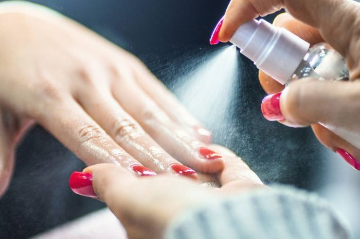 manicurist spraying a substance on customer's nails