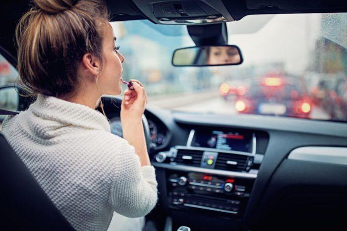 girl woman putting lipstick on in car mirror