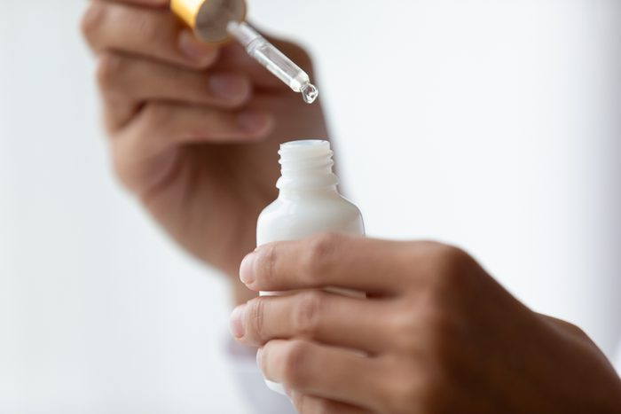 woman's hands holding serum bottle