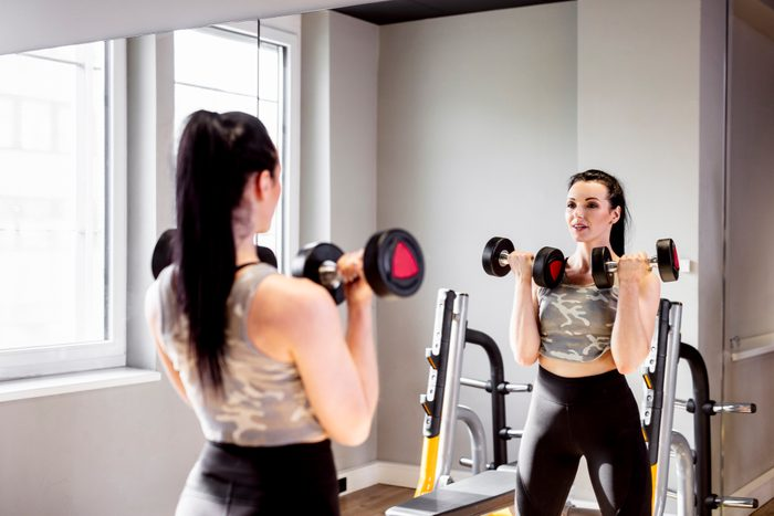 woman looking in mirror at gym while strength training