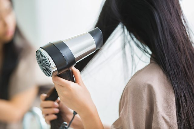woman drying hair with blow-dryer