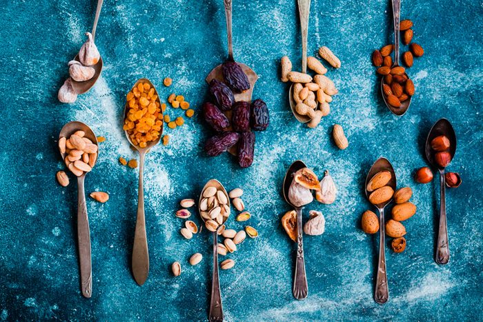 spoons with colorful variety of spices on blue cloth