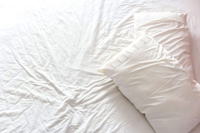 wrinkled bedsheets and pillows