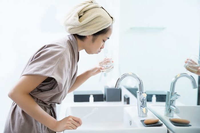 woman in robe gargling over a sink
