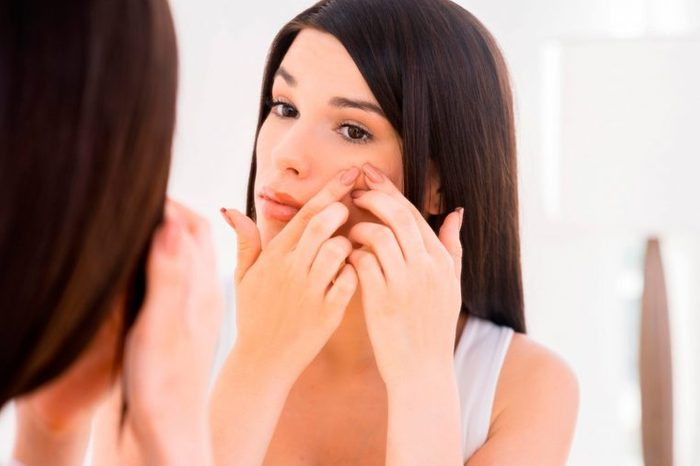 A woman popping an acne pimple in the mirror.
