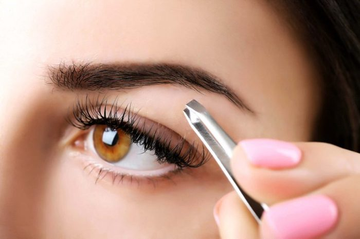 close up of a woman using a tweezer to pluck her eyebrows