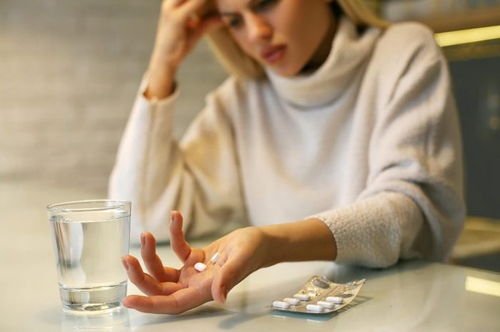woman with pills and glass of water