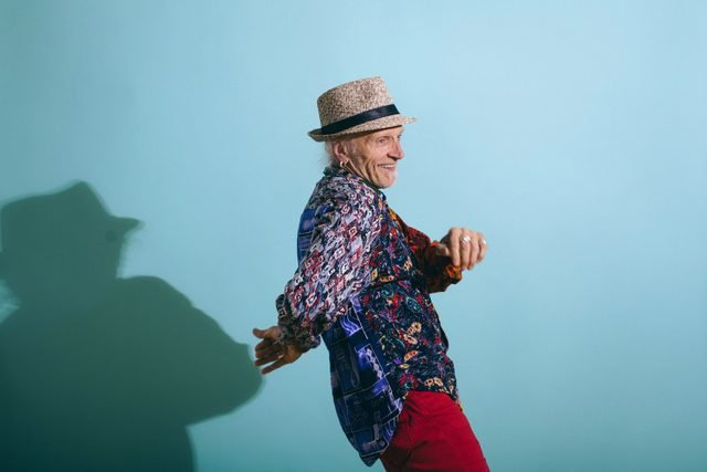 senior man laughing and dancing on blue background