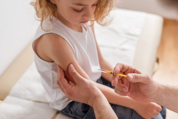 doctor giving a young girl a vaccination
