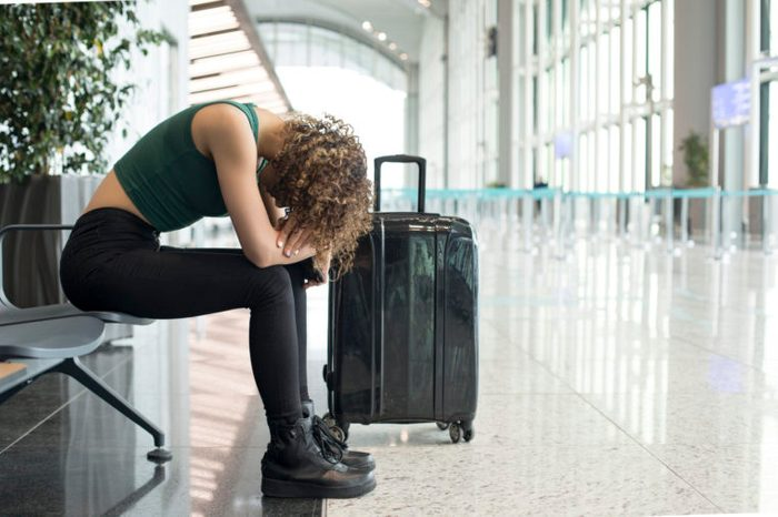 woman sitting in the airport waiting for delayed flight