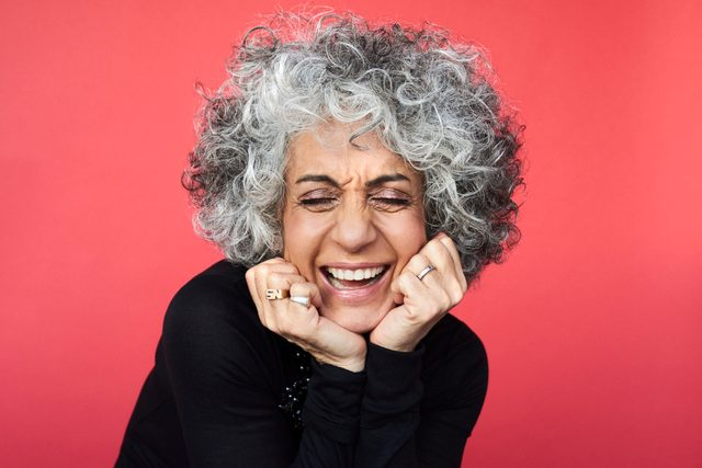 mature woman laughing on red background
