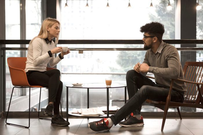two people sitting at a table in a cafe talking to each other