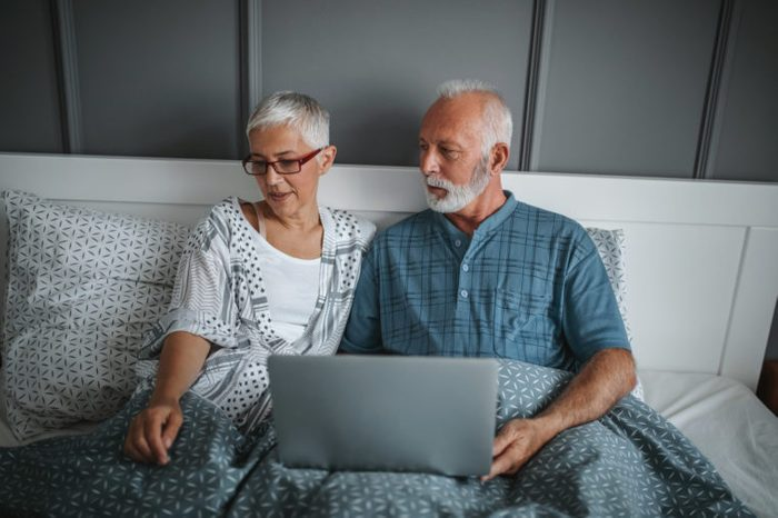 couple in bed talking and using laptop