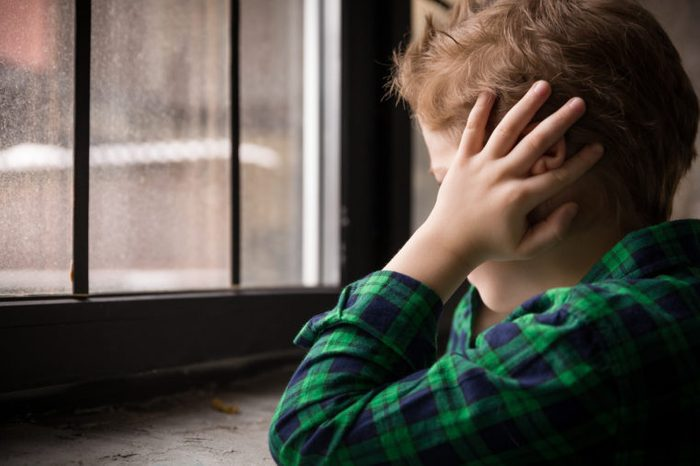 young boy sitting near window with hands over ears