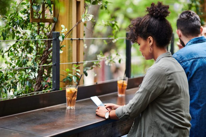 woman sitting at a bar using her phone