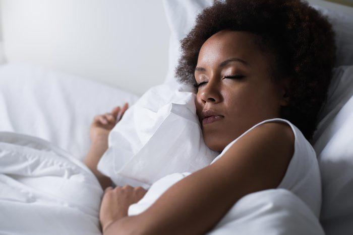 woman sleeping, holding her pillow
