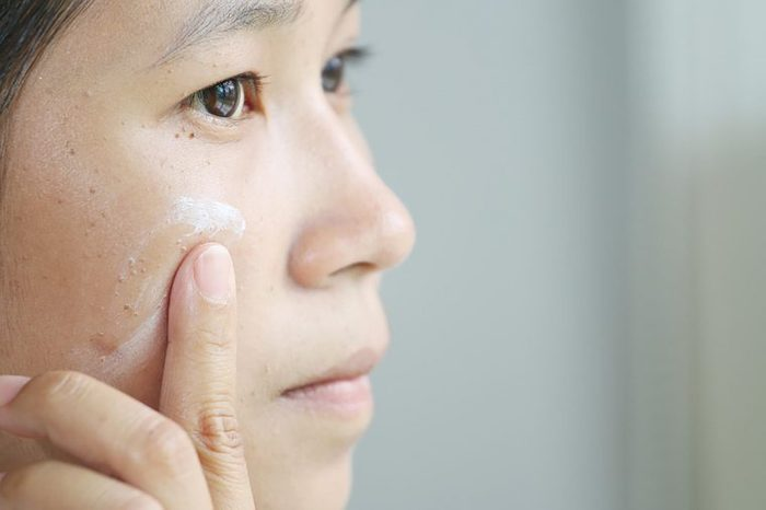 Woman applying foundation to the skin on her cheek.
