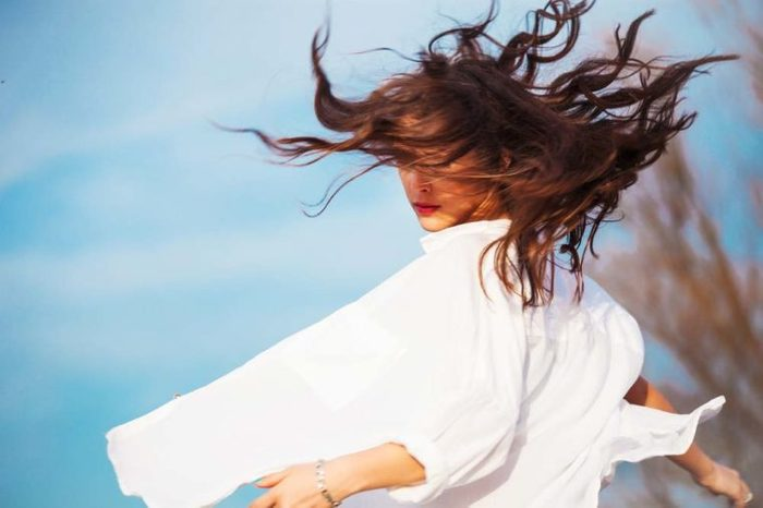 A woman spinning in a circle outdoor with her hair in the wind.
