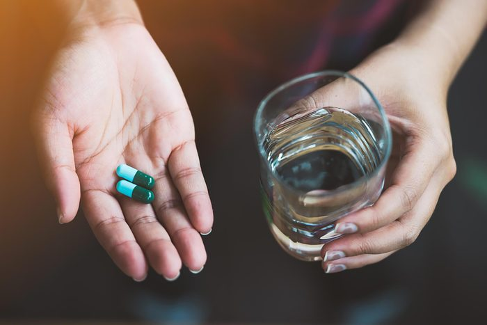 hand holding magnesium capsules and glass of water