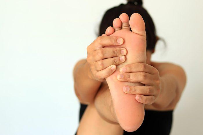woman massaging foot for better circulation