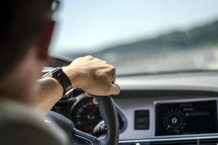 person driving with hand on steering wheel